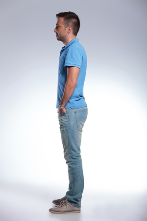 side pose: side view of a young casual man holding his hands in his pockets and looking forward, away from the camera. on gray background