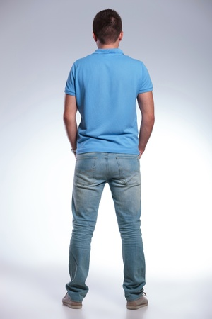 man back view: back view of a young casual man standing with his hands in his pockets. on gray background