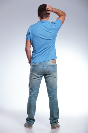 man rear view: back view of a pensive young casual man scratching his head while holding a hand in his pocket. on gray background