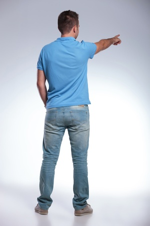 indicating: back view of a young casual man pointing away from the camera. on gray background
