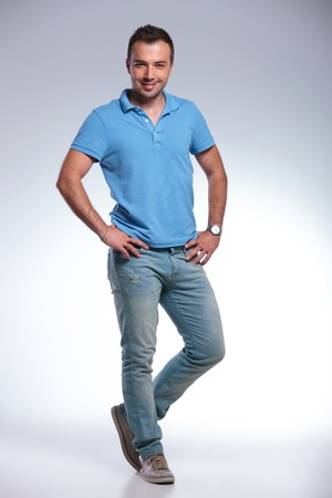 hands on hips: full length picture of a young casual man with his hands on his hips looking into the camera and smiling. on gray background Stock Photo