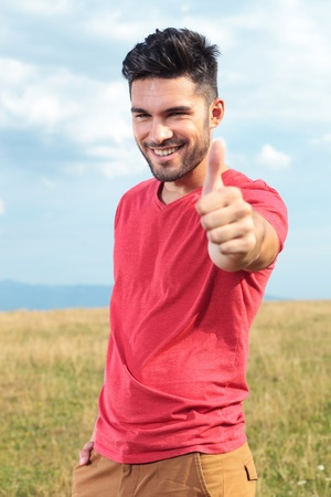 good looking boy: casual young man outdoor showing the thumbs up sign to the camera while smiling Stock Photo