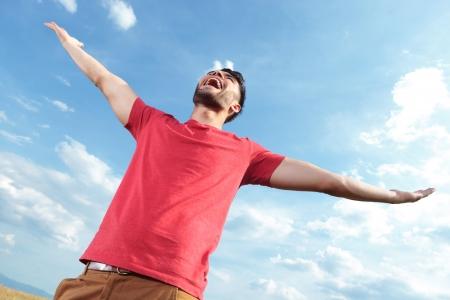 casuale gridare all'aperto giovane uomo al cielo mentre si tiene le sue mani spalancate