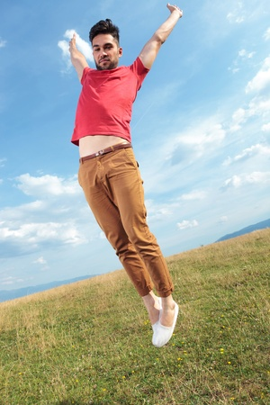 casual young man outdoor jumping with his hands wide open and feet together while looking at the camera photo