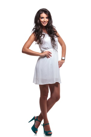 full length picture of a young beautiful woman posing with her hands on her hips and smiling for the camera. isolated on a white background
