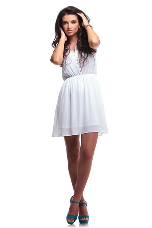 feet crossed: full length picture of a young beautiful woman posing with her hands through her hair and her legs crossed while looking at the camera. isolated on a white background