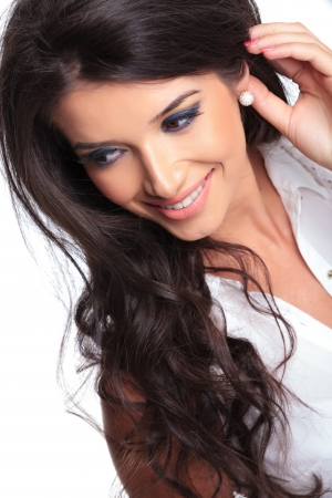 closeup picture of a young beautiful woman looking down and smiling while holding her hand behind her ear. isolated on a white background photo