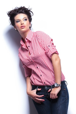 beautiful young woman in jeans and red shirt leaning against white wall and looking away from the camera photo