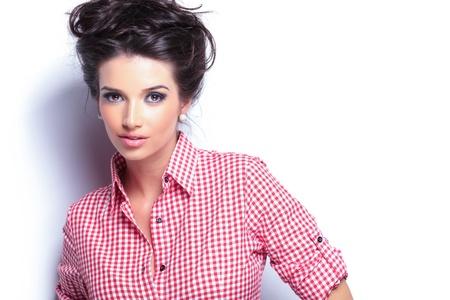 mooie vrouwen: schoonheid van de jonge vrouw in het rood shirt en mooi kapsel kijken naar de camera