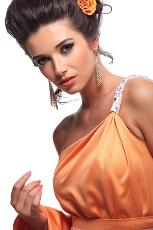 young beautiful woman with beauty makeup and flowers inher hair holding her dress in one hand and looking at the camera photo