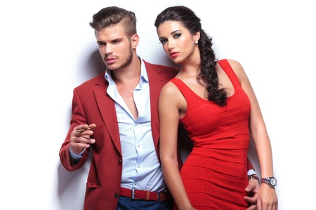 a pair: fashion man and woman, man smoking and looking away and woman looking at the camera. casual couple leaning against a white wall