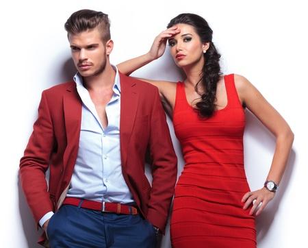 pareja apasionada: joven pareja ocasional contra la pared blanca, el hombre mirando a otro lado y la mujer mirando a la cámara Foto de archivo
