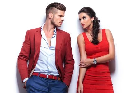 casual mode man en vrouw kijken elkaar terwijl leunend tegen de witte muur