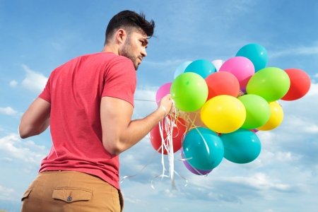 back view of a casual young man holding balloons outdoor and looking to his side photo