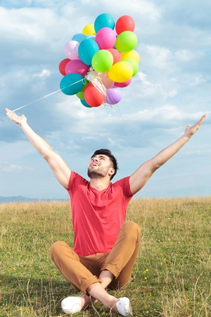 legs crossed: casual young man holding balloons outdoor with arms wide open while looking up Stock Photo