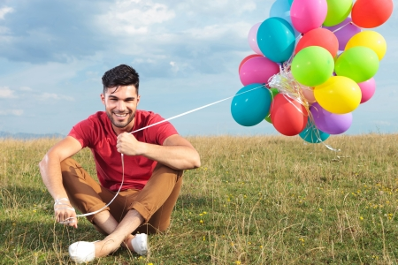man looking out: casual young man sitting outdoor on the grass and holding balloons while smiling for the camera