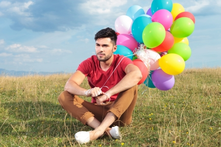 picture of a seated casual young man holding balloons outdoor and looking away from the camera photo