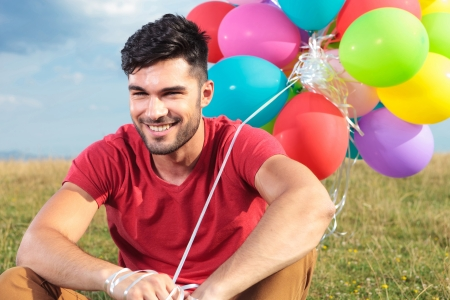 closeup picture of casual young man sitting outdoor on the grass and holding some balloons while smiling for the camera photo