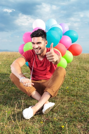 seated casual young man holding balloons outdoor and showing the thumbs up gesture while smiling for the camera photo