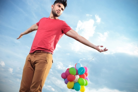 casual young man standing outdoor and holding balloons with his arms wide open while looking away from the camera photo