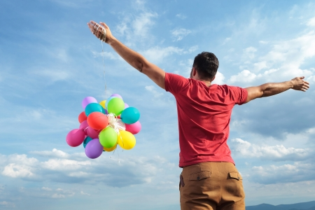 weather balloon: back view of a casual young man holding balloons outdoor with his arms wide open