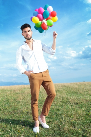 full length picture of a casual young man holding balloons outdoor and a hand in his pocket photo