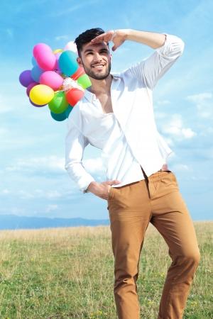 lejos: Hombre joven ocasional celebración de globos al aire libre y mirando a lo lejos mientras mantiene una mano sobre sus ojos y uno en los bolsillos