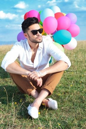 casual young man sitting on the ground with his legs crossed and holding balloons while looking away from the camera  photo