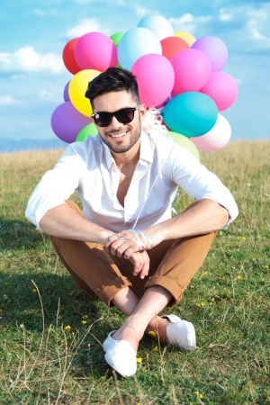 field glass: seated casual young man holding balloons outdoor and smiling for the camera
