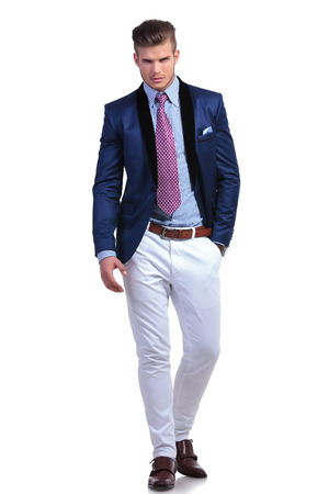 full length photo of a young business man holding a hand in his pocket while looking at the camera. on a white background photo