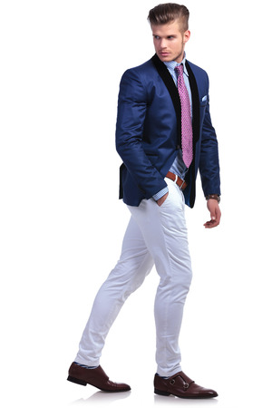 over shoulders: full length portrait of a young business man walking while looking back, away from the camera, and holding a hand in his pocket. on a white background