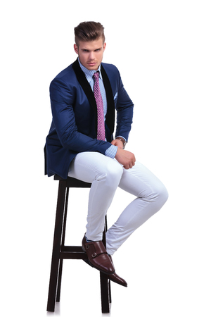 full length photo of a young business man sitting on a high chair and looking into the camera while holding a hand on his hip. on a white background Stock Photo