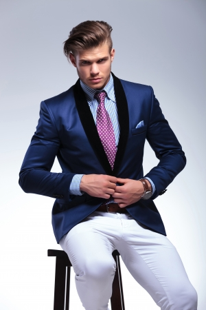 closeup portrait of a young business man sitting on a chair and taking his suit jacket off while looking into the camera. on a gray background photo