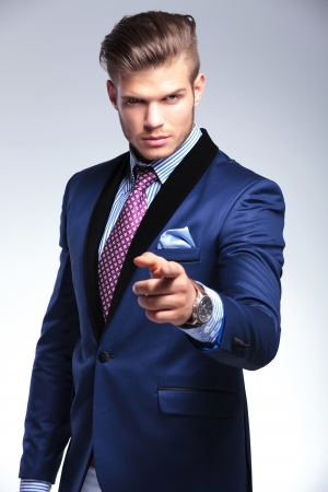 young business man pointing and looking at the camera. on a gray background photo
