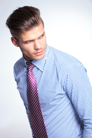 closeup of a young business man looking over his shoulder. on a white background photo