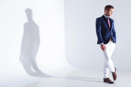 Lunghezza piena vista di un giovane uomo d'affari in cerca di distanza mentre si tiene una mano in tasca. su uno sfondo grigio con ombra Archivio Fotografico