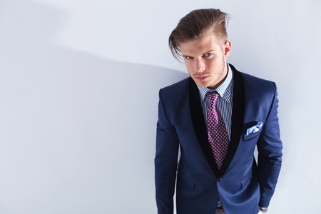 waistup: waist-up portrait of a young business man looking into the camera with a hand in his pocekt. on a gray  studio background