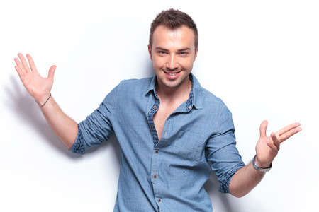 smiling young casual man welcoming with arms opened. on white background photo