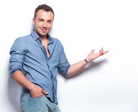 young casual man presenting something while holding a hand in his pocket and smiling for the camera. on white background Stock Photo