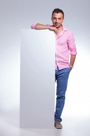 pannel: young casual man holding a pannel and his hand in his pocket while looking into the camera. on gray background