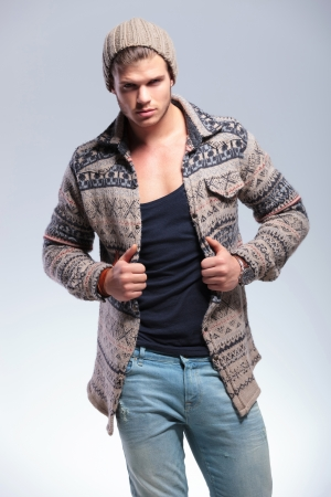 lapels: casual young man looking at the camera while holding his hands on his jacket. on gray background Stock Photo