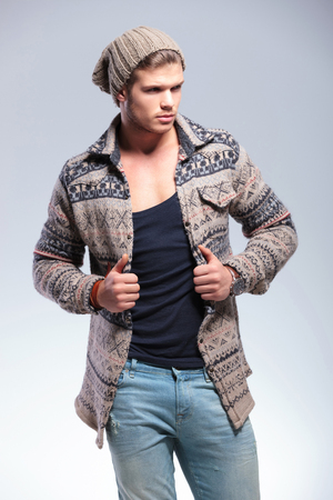 lapels: casual young man looking away while holding his hands on his jacket. on gray background