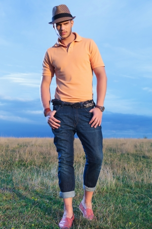 late summer: full length photo of a young casual man outdoor looking into the camera while holding both thumbs in his pockets