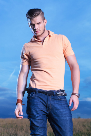 frowned: young casual man posing outdoor, looking frowned into the camera, with the dark blue sky behind him