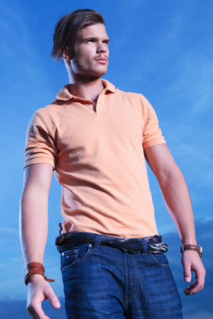 far away look: young casual man posing outdoor, looking away from the camera with the blue sky behind