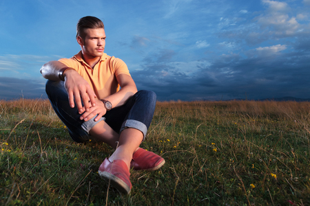 young casual man sitting outdoor in the grass and looking away from the camera while holding his feet crossed photo