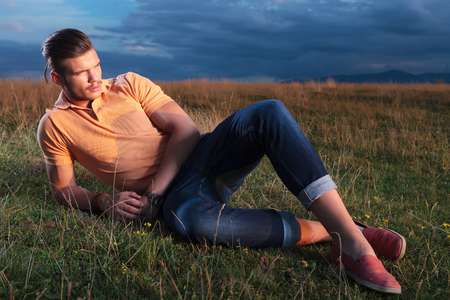 young casual man laying outdoor in the grass and looking away from the camera photo