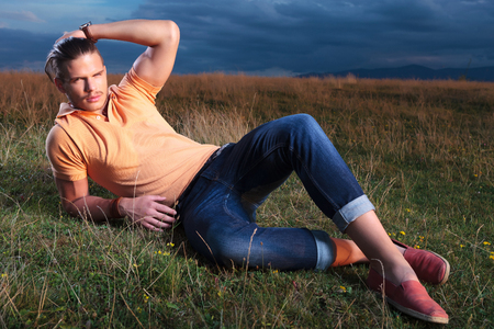 young casual man outdoor laying on the ground and fixing his hair while looking into the camera photo
