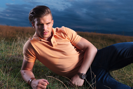 frowned: young casual man laying outdoor on the ground and looking at the camera with a frown on his face Stock Photo