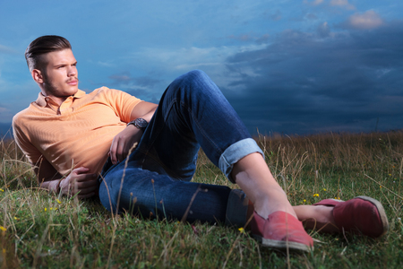 foot model: full length picture of a young casual man laying outdoor in the grass, with his feet crossed, and looking away from the camera